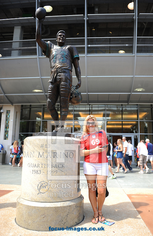 A England fan poses for a photgraph next to the statue of Miami Dolphins former quater back Dan Marino prior to the International Friendly match at Sun Life Stadium, Miami Gardens<br /> Picture by Daniel Hambury/Focus Images Ltd +44 7813 022858<br /> 07/06/2014