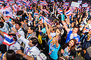 24 JANUARY 2014 - BANGKOK, THAILAND: Thai anti-government protestors cheer for Suthep Thaugsuban when he walked on stage at the Shutdown Bangkok Pathum Wan stage. Shutdown Bangkok has been going for 12 days with no resolution in sight. Suthep, the leader of the anti-government protests and the People's Democratic Reform Committee (PDRC), the umbrella organization of the protests,  is still demanding the caretaker government of Prime Minister Yingluck Shinawatra resign, the PM says she won't resign and intends to go ahead with the election.    PHOTO BY JACK KURTZ