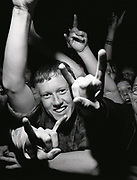 Young man in a crowd smiling with arm raised.