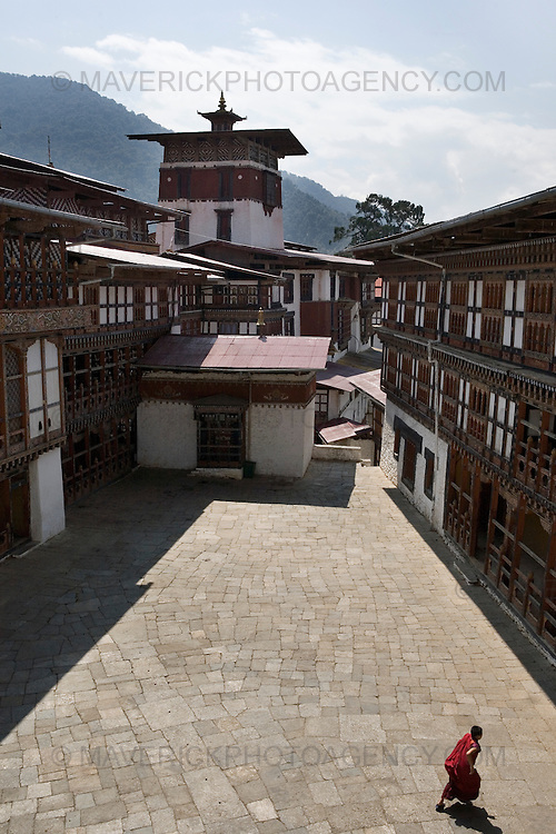 A monk stands in the courtyard of Trongsa dzong, Trongsa..Commonly described as the last Himalayan Shangrila, Bhutan is a country of unique serenity, harmony, and beauty. Nestled between India, China, and Tibet, this independent country whose name translates as 'the Land of the Thunder Dragon' has for the past 300 years  proactively followed a policy of isolation and cultural protection. Travel in and out of the country is strictly regulated, and the impact of outside influences on the local culture is carefully monitored. Spirituality is an important aspect of Bhutanese culture, with Buddhism being interlinked with everyday life. Gross National Happiness (GNH), as opposed to GNP/GDP, forms the cornerstone of its development strategy which focuses on a holistic development strategy that complements its cultural and Buddhist spiritual values.