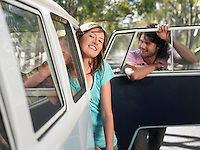 Couple leaning out of van parked by side of road