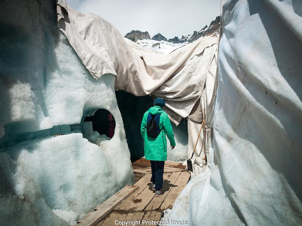 Des personnes se rendent dans la grotte du glacier du Rhone amenage dans la glace le mercredi 27 juin 2013, le glacier est protege par des baches afin de diminuer la fonte des glaces. Depuis 1870, on le perce la grotte chaque annee dans le glacier du Rhone a proximité du col de la Furka. (Olivier Maire)