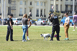 © Licensed to London News Pictures. 25/04/2020. Brighton, UK. People talk to police officers on Brighton seafront at Brighton and Hove, during a pandemic outbreak of the Coronavirus COVID-19 disease.  Photo credit: Liz Pearce/LNP