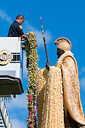 A fireman places long lei on the King Kamehameha Statue in downtown Honolulu, Hawaii.