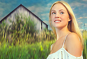 Blonde woman stands proud, smiling while in front of a grey barn with tall yellow reeds in front.  The whole background appears to be moving while she does not.