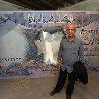"VENICE, ITALY - JUNE 02:  Iraqi artist Walid Siti poses in front of his work ""Beauty spot"" at the Iraq pavillion on June 2, 2011 in Venice, Italy. This year's Biennale is the 54th edition and will run from June 4th until 27 November."