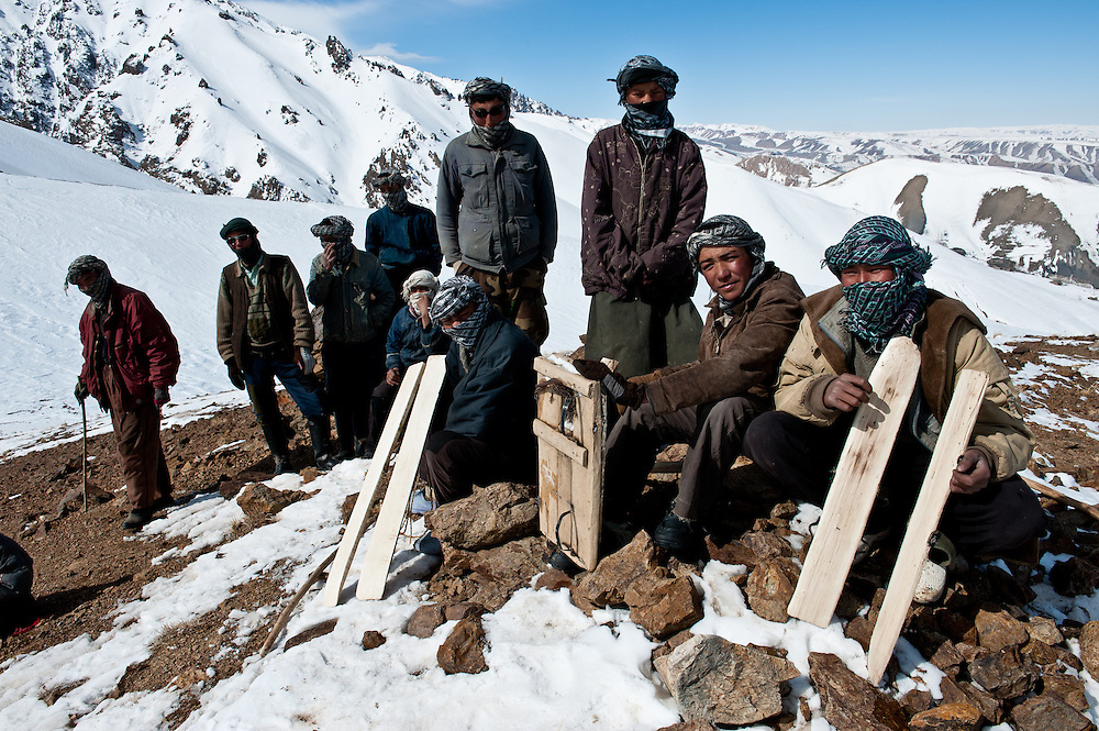Rajab, seated second from right, 15, a villager from Jawzari, made his snowboard by nailing metal from cooking oil cans to a plank from a tree that he cut down himself.