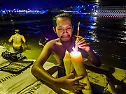 "03 NOVEMBER 2017 - BANGKOK, THAILAND: A Thai man lights incense for people during Loi Krathong near Wat Prayurawongsawat on the Thonburi side of the Chao Phraya River. He takes their krathongs and floats them in the river. People pay him 20Baht (about .70¢ US). for the service. Loi Krathong is translated as ""to float (Loi) a basket (Krathong)"", and comes from the tradition of making krathong or buoyant, decorated baskets, which are then floated on a river to make merit. On the night of the full moon of the 12th lunar month (usually November), Thais launch their krathong on a river, canal or a pond, making a wish as they do so. Loi Krathong is also celebrated in other Theravada Buddhist countries like Myanmar, where it is called the Tazaungdaing Festival, and Cambodia, where it is called Bon Om Tuk.     PHOTO BY JACK KURTZ"