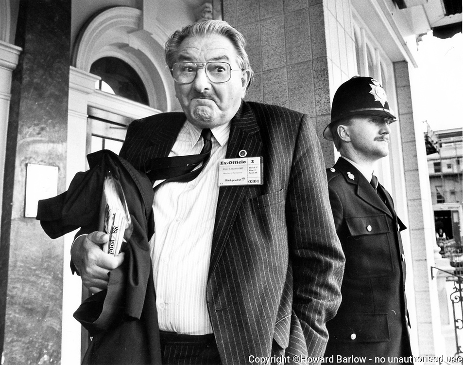 ERIC HEFFER leaves the Imperial Hotel Blackpool, after being kicked off the Labour Party executive in 1988.  I waited nearly three hours for this shot, as it was the story of the day.  When he did emerge from the meeting he swept out, tie flying with that incredible look on his face, the policeman at the door adding to the drama.  Eric Heffer was Labour MP for Liverpool Walton from 1964 until his death in 1991.<br />   Photograph &copy; Howard Barlow