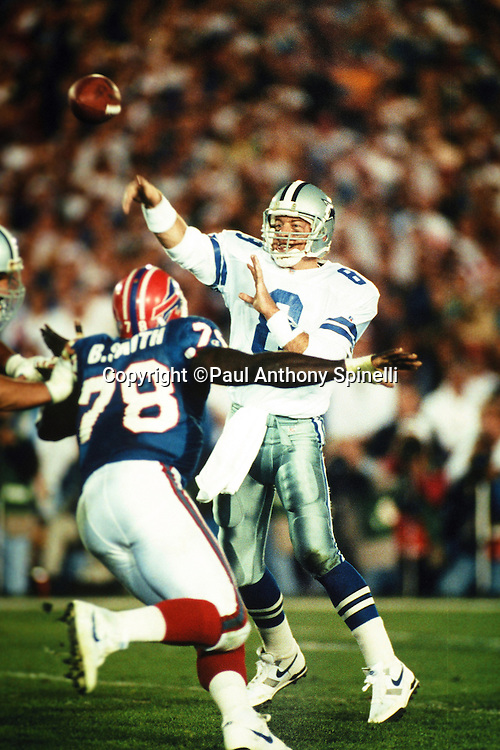 Dallas Cowboys quarterback Troy Aikman (8) throws a pass while pressured by Buffalo Bills defensive end Bruce Smith (78) during the NFL Super Bowl XXVII football game against the Buffalo Bills on Jan. 31, 1993 in Pasadena, Calif. The Cowboys won the game 52-17. (©Paul Anthony Spinelli)