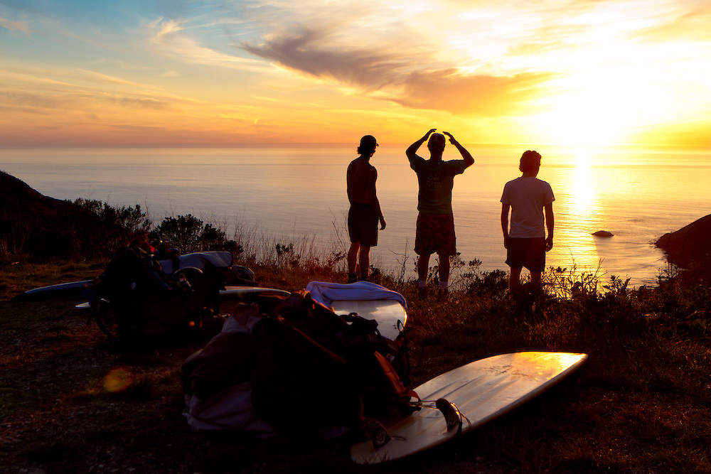 Chris Charney, Matt Schutte, and Andrew Cummins pause to take in the sunset during thier hike into a remote Central Calif., surfing area on Mar. 4, 2012.  (Photo by Aaron Schmidt © 2012)