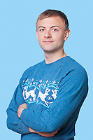 Portrait of young man in sweater with arms crossed against blue background