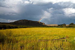 One end of a rainbow and angled storm lighting add to a Middle Park landscape along a US 40 section of the Colorado River Headwaters Scenic Byway in north central Colorado.