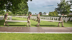 © Licensed to London News Pictures. 07/06/2014. Bayeux, Normandy.  Men and women from the British Army clear up after the ceremony in the British Military Cemetery in Bayeux.  Upto 200 soldiers from 32 Regiment Royal Artillery were tasked with the removal and dismantling of walk ways, marquees and chairs after the event that hosted veterans, guests and members of the Royal household as part of the 70th Anniversary of D Day.  Photo credit : Alison Baskerville/LNP