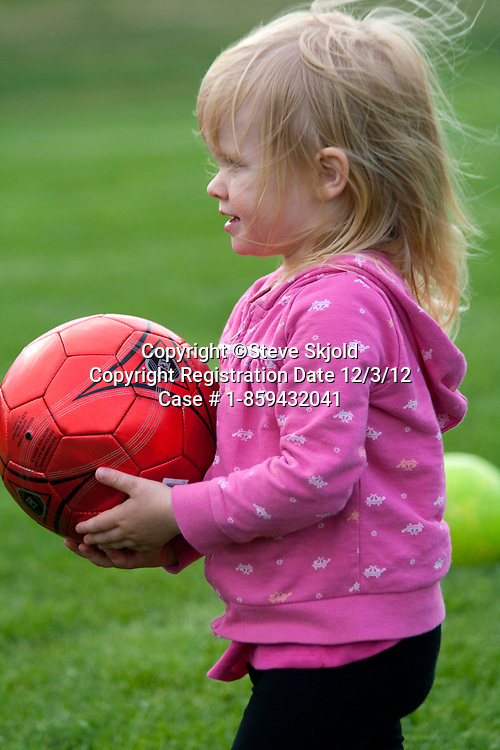 Girl age 2 holding soccer ball on the field Carondelet Field by Expo School St Paul Minnesota MN USA