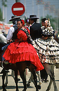 "Riders on horseback, men and women dress up in their finery, the traditional ""traje corto"" (short jacket, tight trousers and boots) for men and the ""faralaes"" or ""trajes de flamenca"" (flamenco style dress) for women. The men traditionally wear hats called ""cordobés""...The Feria de abril de Sevilla, ""Seville April Fair"" dates back to 1847. During the 1920s, the feria reached its peak and became the spectacle that it is today. It is held in the Andalusian capital of Seville in Spain. The fair generally begins two weeks after the Semana Santa, Easter Holy Week. The fair officially begins at midnight on Monday, and runs six days, ending on the following Sunday. Each day the fiesta begins with the parade of carriages and riders, at midday, carrying Seville's citizens to the bullring, La Real Maestranza...For the duration of the fair, the fairgrounds and a vast area on the far bank of the Guadalquivir River are covered in rows of casetas (individual decorated marquee tents which are temporarily built on the fairground). Some of these casetas belong to the prominent families of Seville, some to groups of friends, clubs, trade associations or political parties. From around nine at night until six or seven the following morning, at first in the streets and later only within each caseta, crowds of people party and dance Sevillanas, traditional Flamenco dances, Sevillan style drinking Jerez sherry, or Manzanilla wine, and eating tapas."