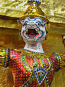 "A demon guards a gilded chedi (or stupa) at the Temple of the Emerald Buddha (Wat Phra Kaew), which is a shining complex of buildings within the grounds of the Grand Palace in Bangkok, Thailand. The Grand Palace (or Phra Borom Maha Ratcha Wang, in Thai) was built on the east bank of the Chao Phraya River starting in 1782, during the reign of Rama I. It served as the official residence of the king of Thailand from the 1700s to mid 1900s. Photo by Carol Dempsey. Published in ""Light Travel: Photography on the Go"" by Tom Dempsey 2009, 2010."