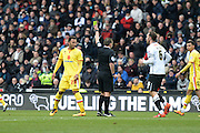 Referee Geoff Eltringham shows MK Dons striker Nicky Maynard a yellow card during the Sky Bet Championship match between Derby County and Milton Keynes Dons at the iPro Stadium, Derby, England on 13 February 2016. Photo by Jon Hobley.