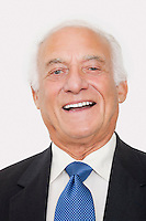 Portrait of happy elderly businessman against white background