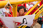 01 JULY 2011 - BANGKOK, THAILAND:  A woman holds a flag showing a likeness of Yingluck Shinawatra, the Pheua Thai candidate for Prime Minister, during a Pheua Thai rally in Bangkok Friday. Thailand's divisive election campaign drew to a close Friday in Bangkok. Most of the parties had large rallies in an effort to sway last minute undecided voters. Pheua Thai, the party of ousted Prime Minister Thaksin Shinawatra held a massive rally in Rajamakala Stadium (also called Ramkamhaeng Stadium) to close out their campaign. A monsoon thunderstorm didn't keep people away from the event. Most Thai public opinion polls show Pheua Thai with a healthy lead over their arch rivals (and incumbent party in power) the Democrats. Thaksin's youngest sister, Yingluck Shinawatra, is running for Prime Minister under the Pheua Thai banner. If elected, she will be Thailand's first female Prime Minister.      PHOTO BY JACK KURTZ
