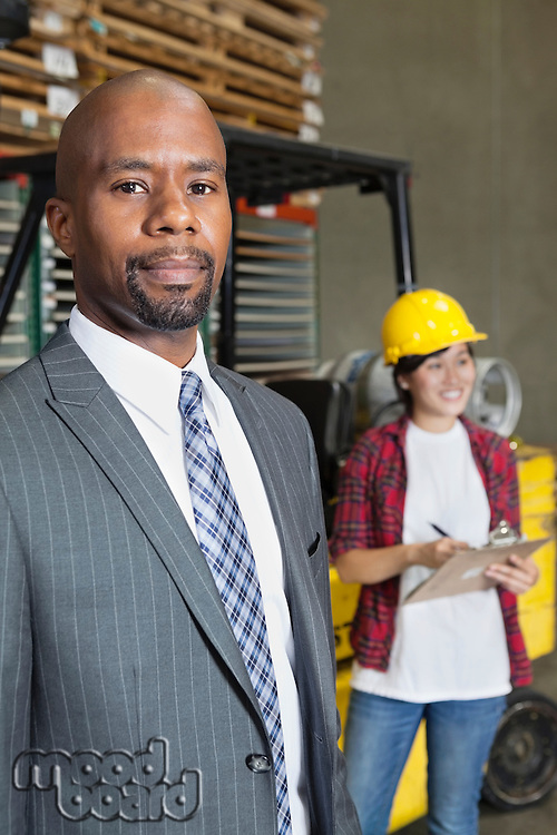Portrait of confident African American male businessman with female worker standing in background
