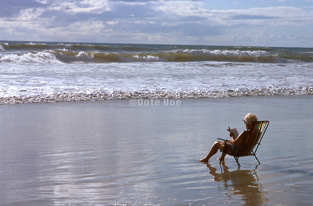 Seascape of the ocean with a person relaxing on the beach
