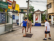 18 FEBRUARY 2015 - BANGKOK, THAILAND: Boys play soccer in the Kudeejeen neighborhood in Bangkok. Santa Cruz church was established in 1770 and is the heart of the community. It is one of the oldest and most historic Catholic churches in Thailand. The church was originally built by Portuguese soldiers allied with King Taksin the Great. Taksin authorized the church as a thanks to the Portuguese who assisted the Siamese during the war with Burma. Most of the Catholics in the neighborhood trace their family roots to the original Portuguese soldiers who married Siamese (Thai) women. There are about 300,000 Catholics in Thailand in about 430 Catholic parishes and about 660 Catholic priests in Thailand. Thais are tolerant of other religions and although Thailand is officially Buddhist, Catholics are allowed to freely practice and people who convert to Catholicism are not discriminated against.   PHOTO BY JACK KURTZ