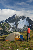 Adult male hiker in red shirt at backcountry camp on Red Face Mountain, Whatcom Peak seen in the distance. North Cascades National Park Washington