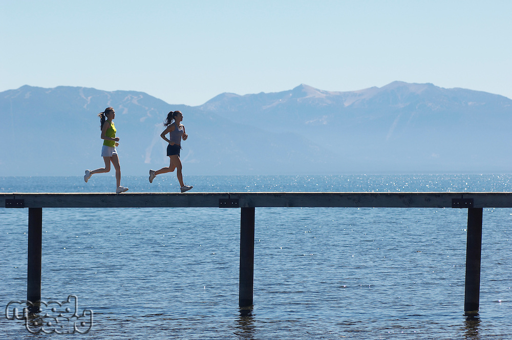 Two women running along a pier with mountains behind side view