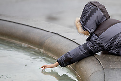 © Licensed to London News Pictures. 23/01/2017. London, UK. People poke the ice in the Trafalgar Square fountains, which have frozen over this morning. Thick fog has covered London, whilst temperatures drop to -2 degrees celsius. Photo credit : Tom Nicholson/LNP