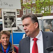 Amsterdam, 21-09-2013.  Vanuit 16 steden in het land kwamen bussen naar Amsterdam met betogers die meededen aan de demonstratie tegen de geplande bezuinigingen van het kabinet. De organisatie Comité Stop Bezuinigingen schatte de opkomst op ongeveer 5000 mensen. De manifestatie begon op het Beursplein. Vandaar trokken de demonstranten naar het beeld van de Dokwerker op het Jonas Daniël Meijerplein. Daar werd gesproken door onder andere SP-leider Emile Roemer en Henk Krol (50Plus). Meer dan 50 maatschappelijke organisaties hebben hun steun toegezegd aan de protestactie. Onder meer de Amsterdamse afdelingen van FNV Bondgenoten, Abvakabo FNV en SP en GroenLinks namen het initiatief tot de demonstratie. Zij menen dat de bevolking ,,het niet langer pikt'' dat de regering weer miljarden wil bezuinigen op onder meer zorg en kinderopvang. Volgens het comité worden de kosten van de crisis afgewenteld op kwetsbare groepen in de samenleving en worden ,,bonussen, belastingontwijking en de topinkomens nauwelijks aangepakt''. Op de foto: Emile Roemer praat met demonstranten.