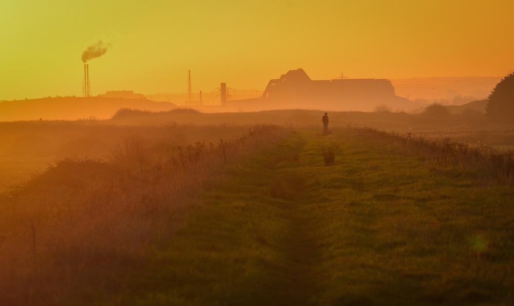 man walking along pathway at sunset