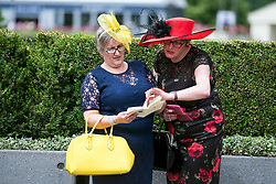 © Licensed to London News Pictures. 19/06/2018. London, UK.  Two Racegoers look at the race program while attending day one of Royal Ascot at Ascot racecourse in Berkshire, on June 19, 2018. The 5 day showcase event, which is one of the highlights of the racing calendar, has been held at the famous Berkshire course since 1711 and tradition is a hallmark of the meeting. Top hats and tails remain compulsory in parts of the course. Photo credit: Ben Cawthra/LNP