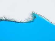 Wave of blue liquid against white background surface view