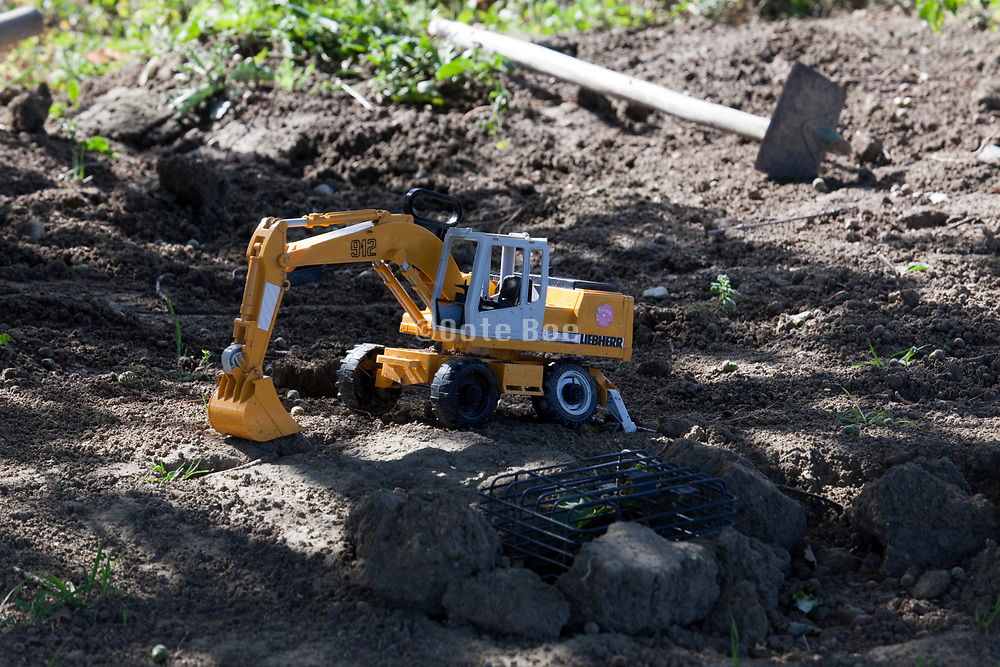realistic toy construction digger with an old shovel in the background