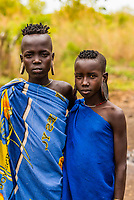 Teenaged girls with ear modifications to hold a clay disc, Mursi tribe, Mago National Park, Omo Valley, Ethiopia.