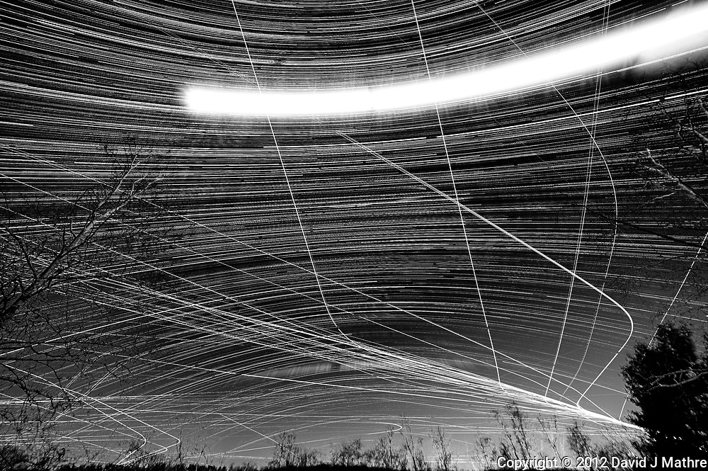 Star, moon, and jet trails looking south from my deck. Composite of 361 images taken with a Nikon D3x camera and 14-24 mm f/2.8 lens (ISO 400, 24 mm, f/4, 59 sec). Raw images processed with Capture One Pro (including conversion to B&W), and the composite created using Photoshop CC (scripts, statistics, maximum).