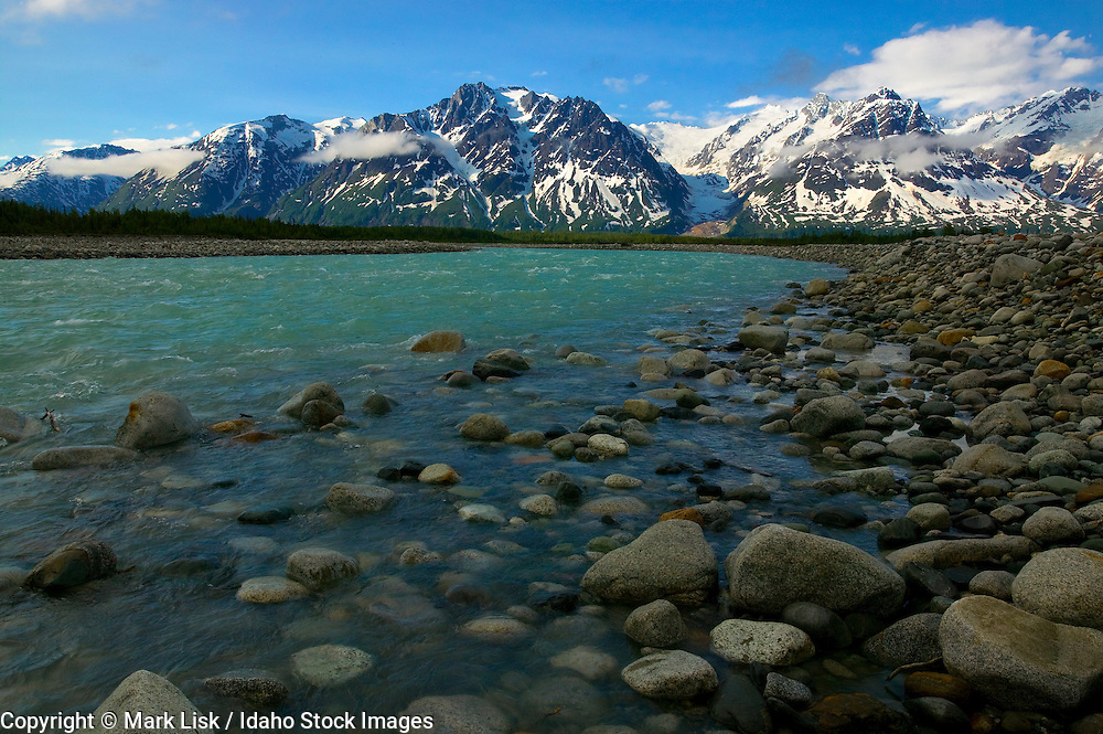 The Alsek and Fairweather ranges of Canada and Alaska tower over the rocky debris at the Melt Creek delta near its confluence with the Tatshenshini River.