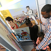 Jade Rucker, 10, from left, her sister, Jaelyn, 5, and father, Brian, check out the comic book style timeline of the Elvis Presley story at the newly renvoated Convention and Vistors Bureau Thursday.