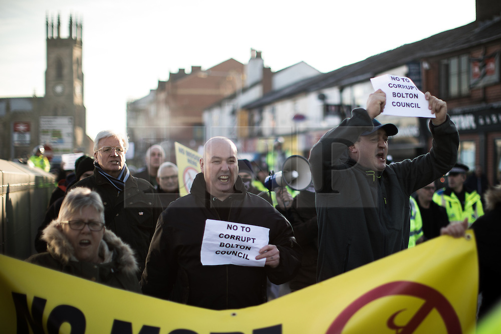 """© Licensed to London News Pictures . 26/11/2016 . Bolton , UK . Anti-mosque demonstrators march from Bolton station to Victoria Square . Approximately 100 people attend a demonstration against the construction of mosques in Bolton , under the banner """" No More Mosques """" , organised by a coalition of far-right organisations and approximately 150 anti fascists opposing the demonstration , in Victoria Square in Bolton Town Centre . Photo credit : Joel Goodman/LNP"""