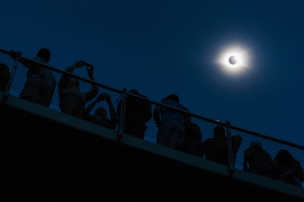 Crowds of people gaze and snap photos of totality during the great American eclipse in Greenville, SC., on Monday, August 21, 2017.