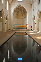 Interior of the Musee d'Art Paien in Arles, France, featuring a beautiful reflecting pool.