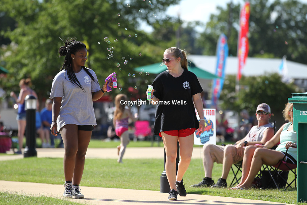 Jocelynn Staples, 18, left, and Cary Cox, 17, from House of Bounce in Saltillo use blowers to blow bubbles as they walk around the All America Picnic at Fairpark on Tuesday.