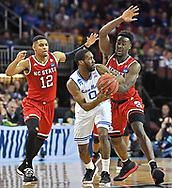 Seton Hall Pirates guard Khadeen Carrington (0) receives pressure from North Carolina State Wolfpack guard Allerik Freeman (12) and forward Abdul-Malik Abu (0) during the first half in the first round of the 2018 NCAA Tournament at INTRUST Bank Arena.