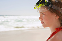 Girl (7-9) in swimming goggles on beach close-up