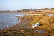 River Deben landscape with small beached dinghy boat at Methersgate,  near Woodbridge, Suffolk, England