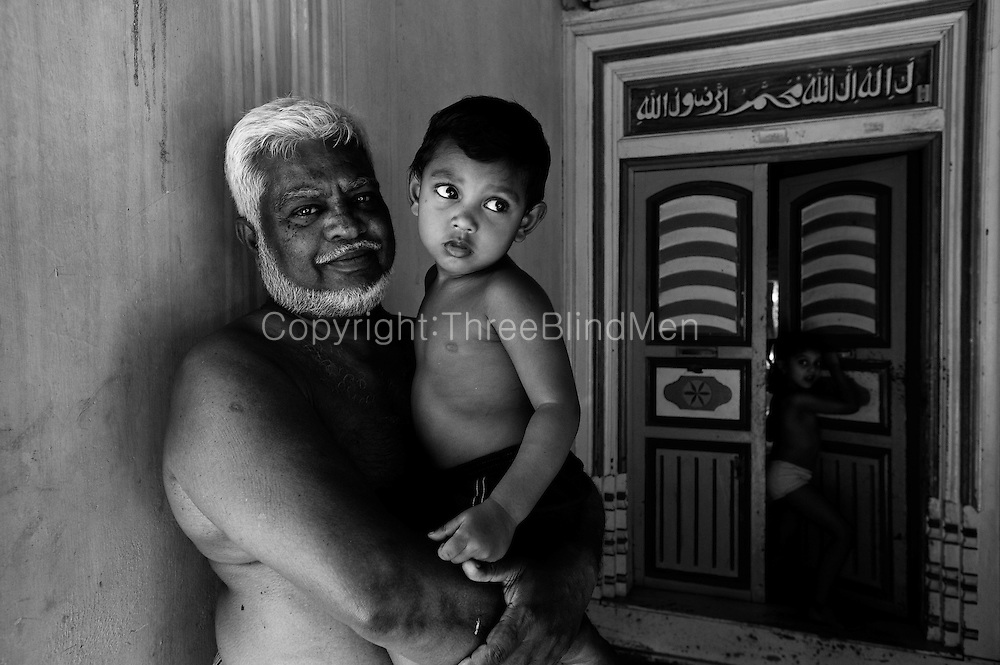 Grandfather and grandchild. Home at Thittacheri. Tamil Nadu. South India.
