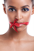 Portrait of beautiful young woman with ribbon tied over her mouth against white background