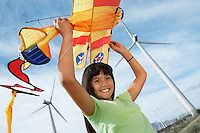 Girl (7-9) holding airplane kite at wind farm