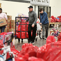 Adam Robison | BUY AT PHOTOS.DJOURNAL.COM<br /> Shane Harrington and his son Hogan, 18, work together to get Angel Tree gifts to moved to the front of Tupelo Furniture Market Building 5 during the Salvation Army Angel Tree pick up Friday morning in Tupelo.